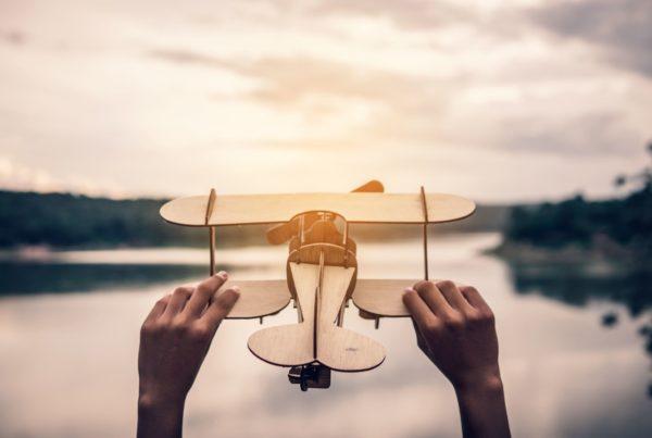 Manos sujetando un avión de madera en la naturaleza