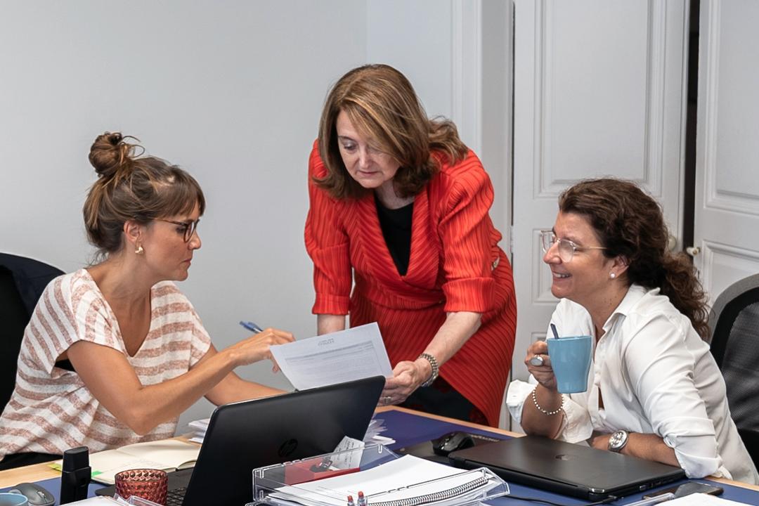 Carmen Mur, fundadora de Mur&Partners, en la oficina de Barcelona revisando documentación junto a dos integrantes de su equipo de Recursos Humanos.