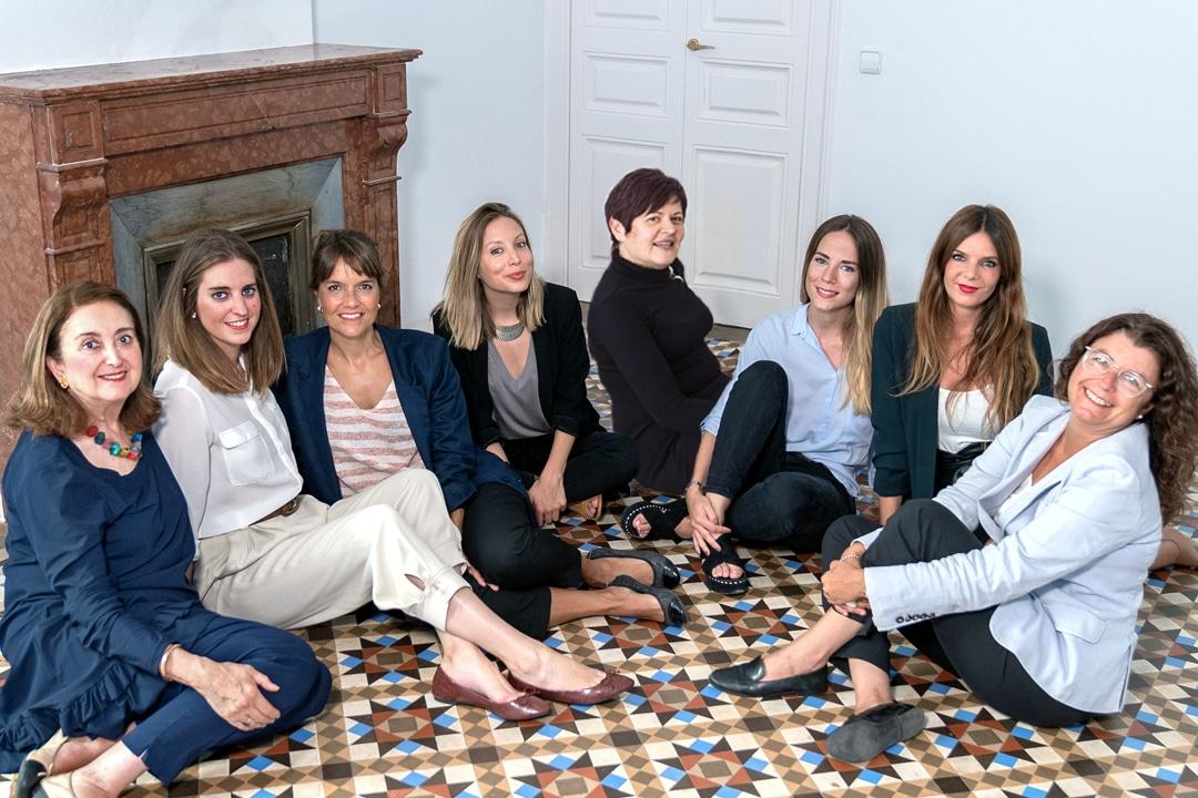 Carmen Mur y todo el equipo de consultoras de recursos humanos de Mur&Partners posando sentadas sobre el precioso suelo de baldosas en la sede de Barcelona.