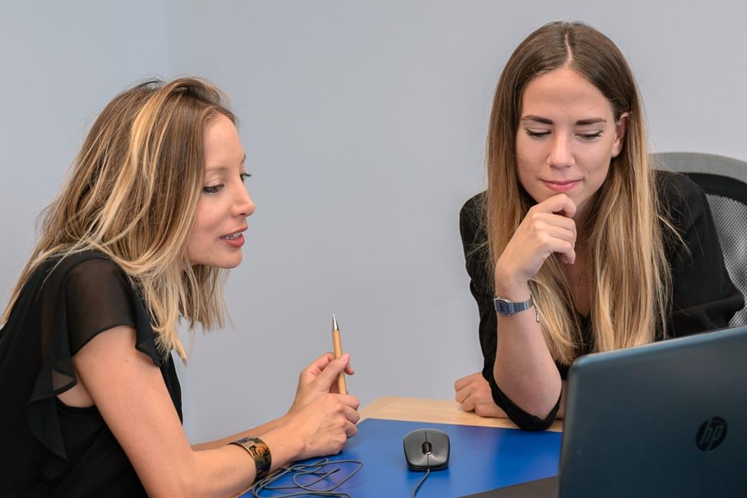 Nerea Madrid y Cristina Diaz, consultoras de recursos humanos de Mur&Partners, revisando información en un ordenador portátil.